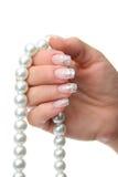 Woman hand holding pearl jewelery Royalty Free Stock Photo