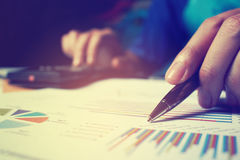 Woman hand holding pen pointing on summary report chart and doin Royalty Free Stock Images