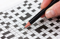 Woman hand holding a pencil and solves crossword Royalty Free Stock Photo