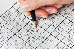 Woman hand holding a pencil and solves crossword sudoku Royalty Free Stock Images