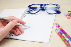 Woman hand holding pencil and writing notebook Stock Photos