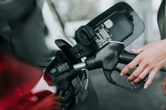 Woman hand holding petrol pump nozzle outdoor. Close up female arm refueling the contemporary auto in petrol cap. She locating on filling station royalty free stock photos
