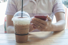 Woman hand holding phone with background of iced coffee Stock Image
