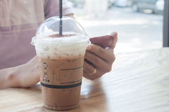 Woman hand holding phone with background of iced coffee Stock Images