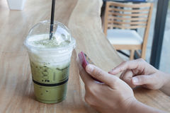 Woman hand holding phone with background of iced green tea Stock Image