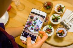 Woman hand holding phone taking photo of tasty Cupcakes with berries. Instagram photography blogging and sweets concept royalty free stock image