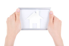 Woman hand holding photo frame with paper house isolated on whit Stock Image