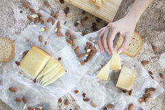 Woman hand holding a piece of cheese, toasts and almonds Stock Photo