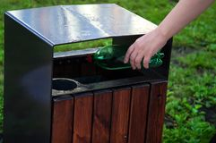 Woman hand holding plastic bottle in trash can Stock Photos