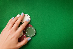 Woman hand holding poker chips on green casino felt background royalty free stock images