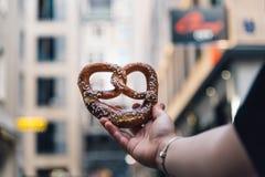 Woman hand holding a pretzel against cityscape. stock images