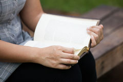 Woman hand holding and reading a book. In the nature park Stock Images