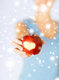 Woman hand holding red apple with heart shape Stock Images