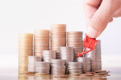 Woman hand holding red watering can on money stack. stock image
