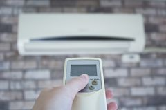 Woman hand holding a remote control directed on air conditioner. royalty free stock photography