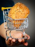 Woman hand holding shopping cart with bread stock photo