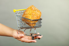 Woman hand holding shopping cart with bread. Buying gluten food products concept. Woman hand holding shopping cart trolley with small piece of bread Royalty Free Stock Photo