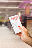 Woman hand holding shopping list. In supermarket or hypermarket Royalty Free Stock Photos