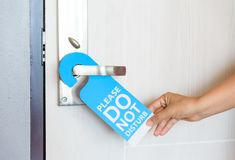 Woman hand holding signboard do not disturb hanging on the door. stock photo