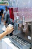 Woman hand holding a small white cup and taking red sweetened dr. Ink in clear plastic container from the beverage dispenser machine Royalty Free Stock Photo