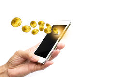 Woman hand holding smart phone and earning coins Stock Photos