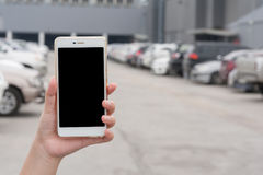 Woman hand holding smartphone in car parking area. Woman hand holding smartphone with blank screen on blurry background of car parking area. Find my car by using royalty free stock photos