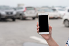 Woman hand holding smartphone in car parking area. Woman hand holding smartphone with blank screen on blurry background of car parking area. Find my car by using stock photos