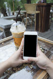 Woman hand holding a smartphone with isolate black screen,at coffee cafe Royalty Free Stock Images