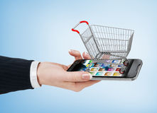 Woman hand holding smartphone with shopping cart. E-commerce con Stock Image