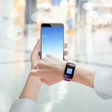 Woman hand holding smartphone wearing smart watch with email ico Stock Photo