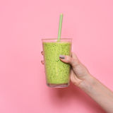 Woman hand holding smoothie shake against pink wall. Stock Image