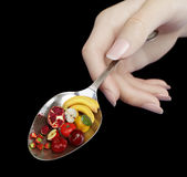 Woman hand holding spoon with fruits on isolate black diet concept photo closeup royalty free stock images