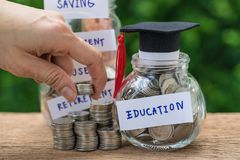 Woman hand holding stack of coins money and glass jar with full. Of coins and graduates hat label as Education, education or savings concept Stock Images