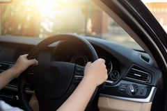 Woman hand holding steering wheel with sunlight Royalty Free Stock Photos