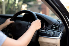 Woman hand holding steering wheel with sunlight Stock Photos