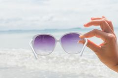 Woman hand holding sunglasses over sea and Sandy beach Stock Photo