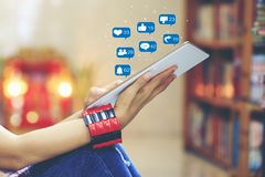 Woman hand holding tablet smart device for checking social media with icon or hologram in library room and bookshelf background, royalty free stock photos