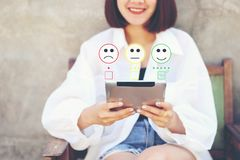 Woman hand holding tablet smart device with putting check mark with smiley face marker in coffee shop, Satisfaction evaluation and. Customer experience concept stock photos