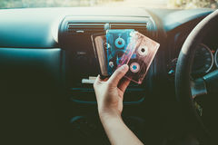 Woman hand holding tape cassette in car for driving listen music. Vintage color tone effect royalty free stock photos