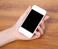 Woman hand holding a touch white phone with with black screen Stock Photography