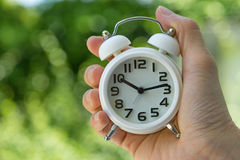 Woman hand holding a white alarm clock  as business or time coun Stock Photo
