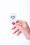 Woman hand holding a white card. On white background, heart Royalty Free Stock Images
