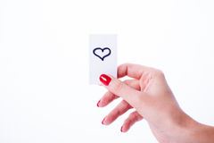 Woman hand holding a white card. On white background, heart Royalty Free Stock Photography