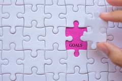 Woman Hand holding white jigsaw puzzle piece with words GOALS. Business resolutions, success, goals and strategy royalty free stock photos