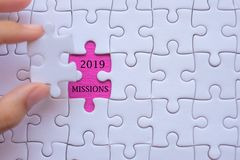 Woman Hand holding white jigsaw puzzle piece with words 2019 MISSION. Business resolutions, success, goals, New Year New Start and stock images