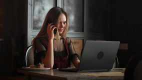 Woman hand holding white mobile phone on a table with a laptop in office. stock video footage