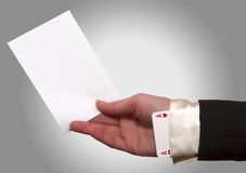 Woman hand holding a white paper. With ace up the sleeve Stock Photography