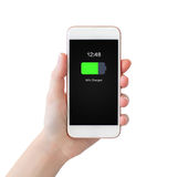 Woman hand holding white phone with charged battery on screen Royalty Free Stock Images