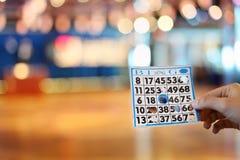 Woman hand holds bingo card Stock Photo
