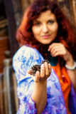 Woman hand holds a fir-cone on wood background, Ecology concept Royalty Free Stock Photography